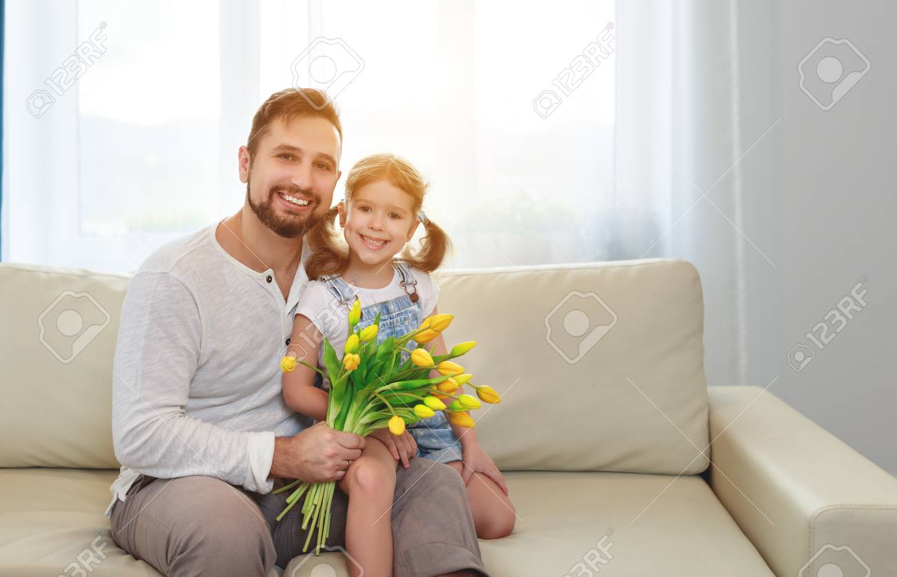 father and child daughter with a bouquet of flowers at home - 97622308