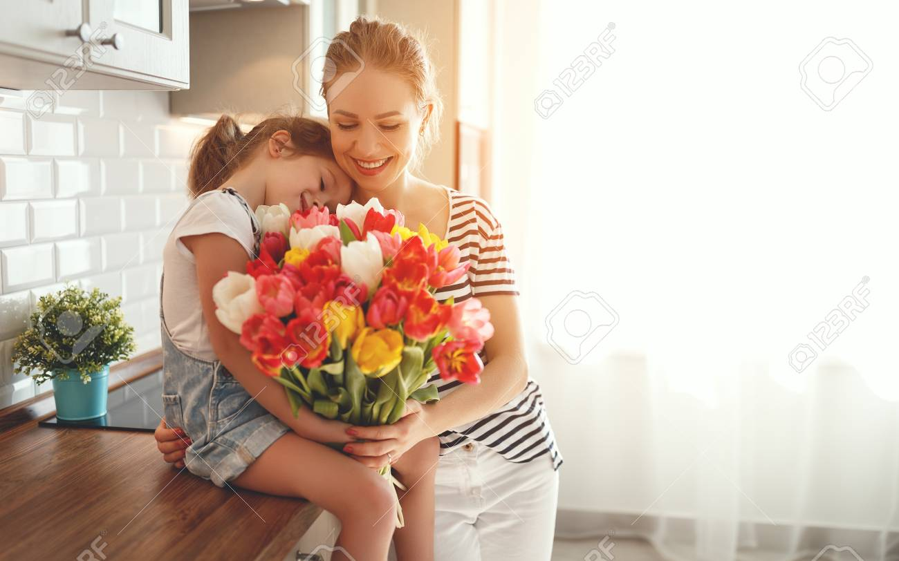 happy mother's day! child daughter congratulates mother and gives a bouquet of flowers to tulips - 97650064