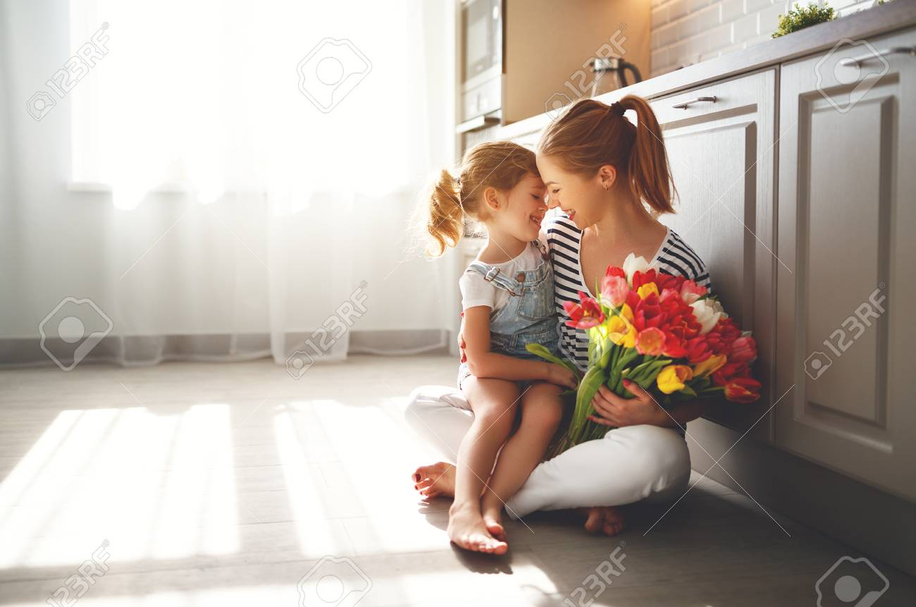 happy mother's day! child daughter congratulates mother and gives a bouquet of flowers to tulips - 98355457