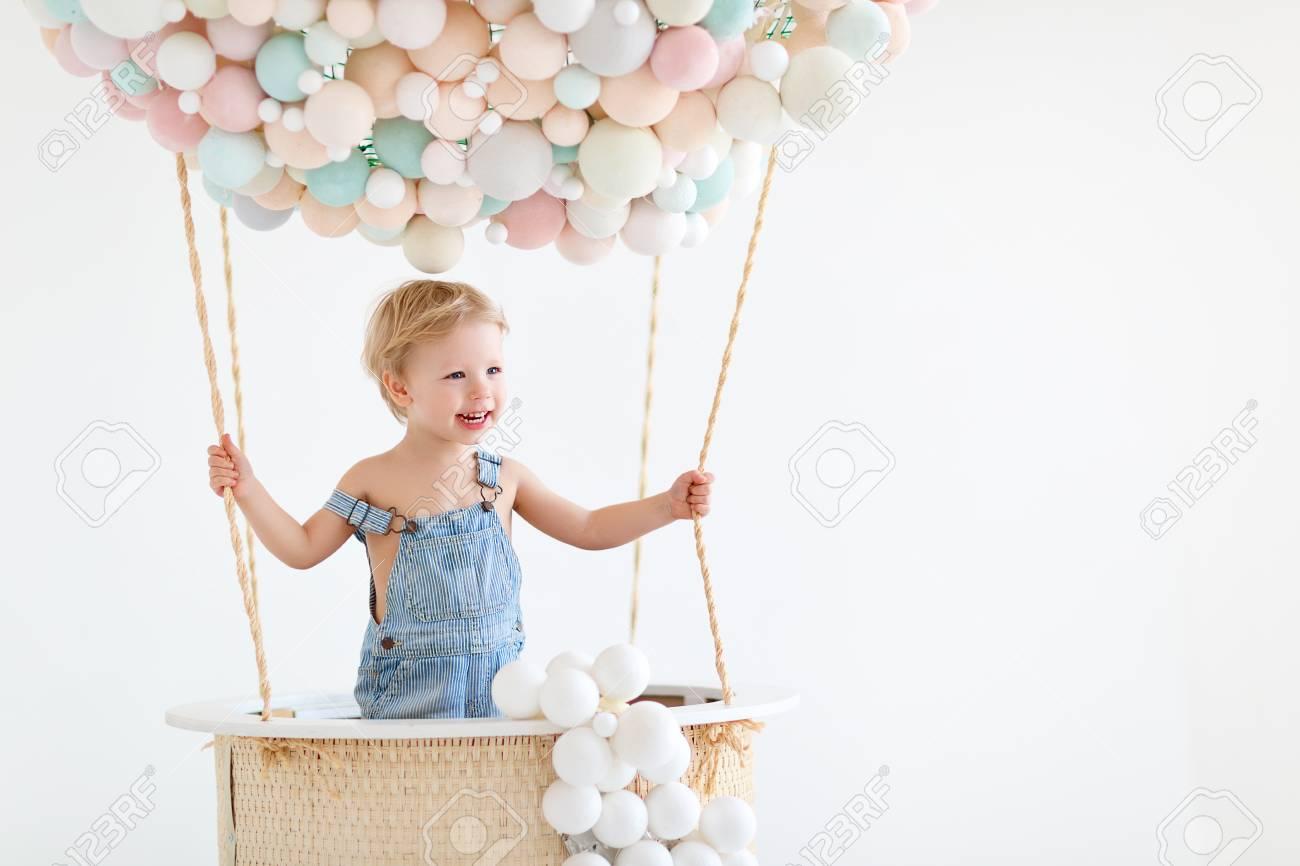 cute happy baby boy in a fairy magic hot air balloon - 100274902
