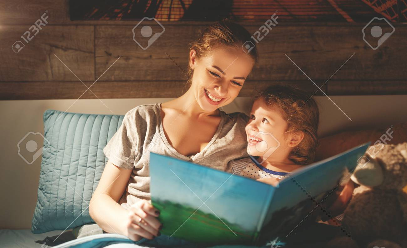 mother and child daughter reading book in bed before going to sleep - 100277136