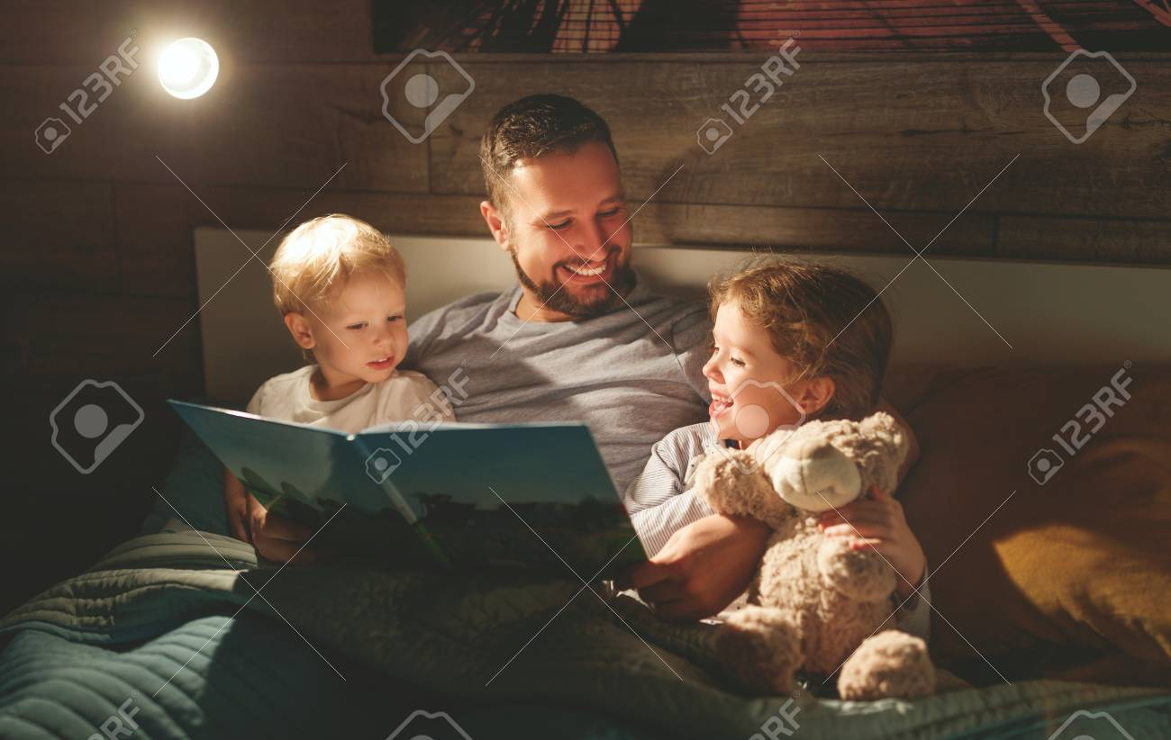 evening family reading. father reads children a book before going to bed - 100277151