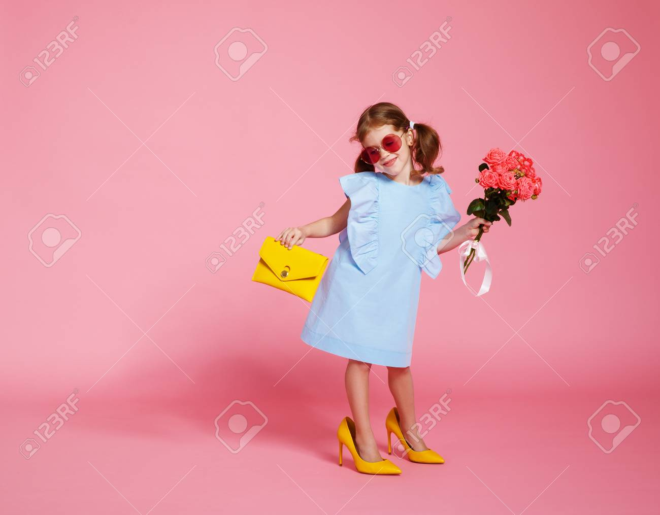 funny child girl fashionista in big mother's yellow shoes on colored background - 101297462