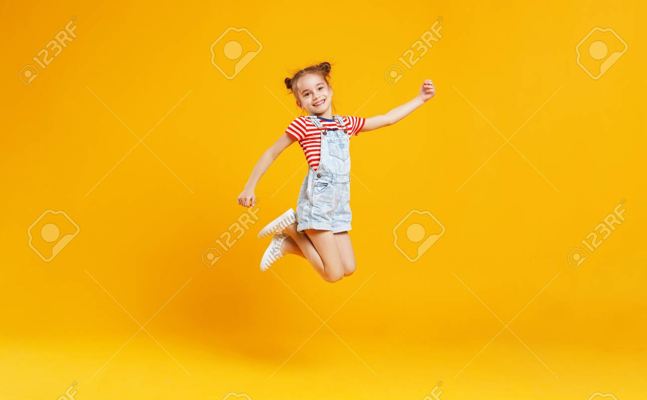 funny child girl jumping on a colored yellow background - 102568647