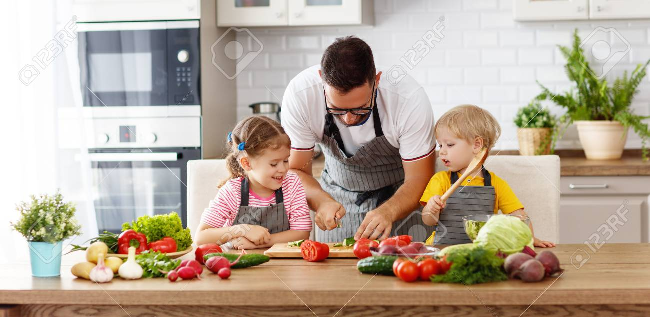 Father with children preparing vegetable salad at home - 103907103