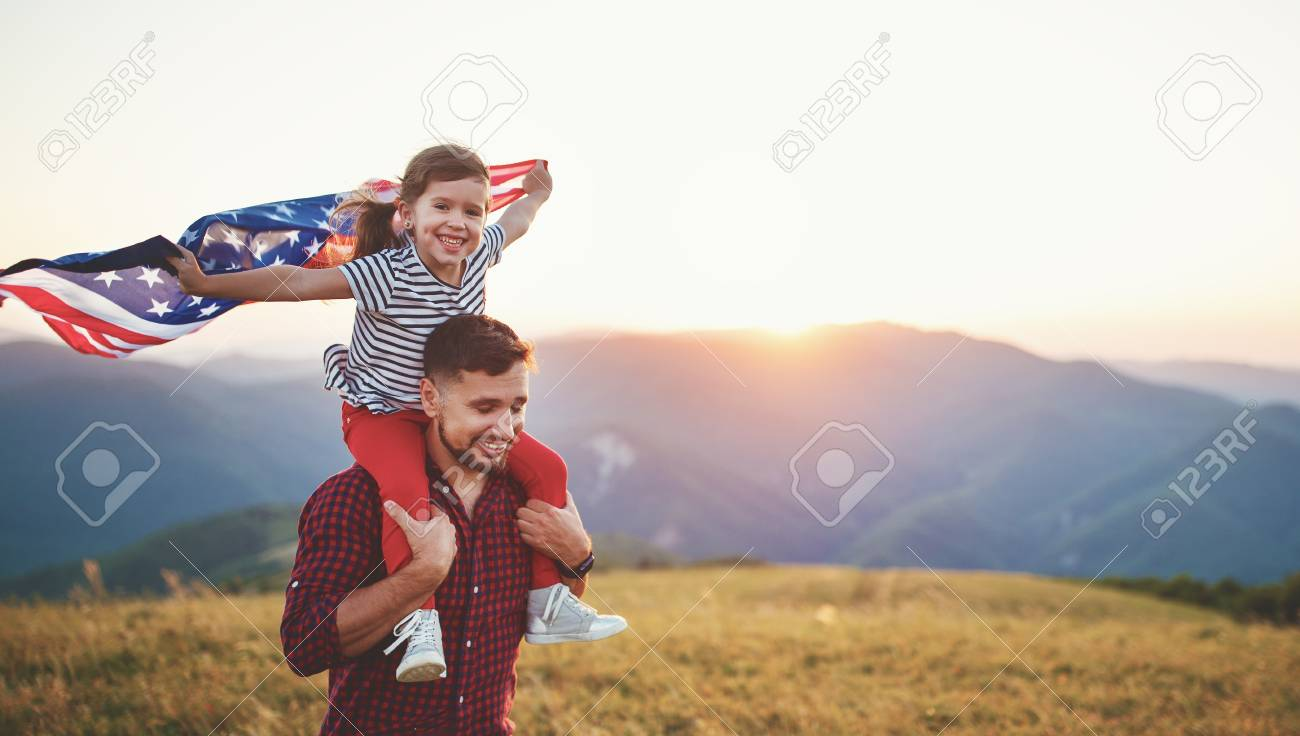 Happy family father and child with flag of united states enjoying sunset on nature - 103907110