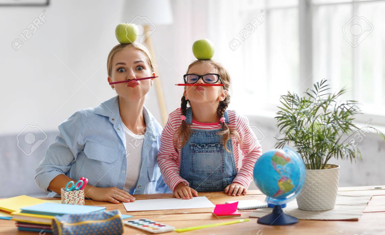 funny mother and child daughter doing homework writing and reading at home - 107007167