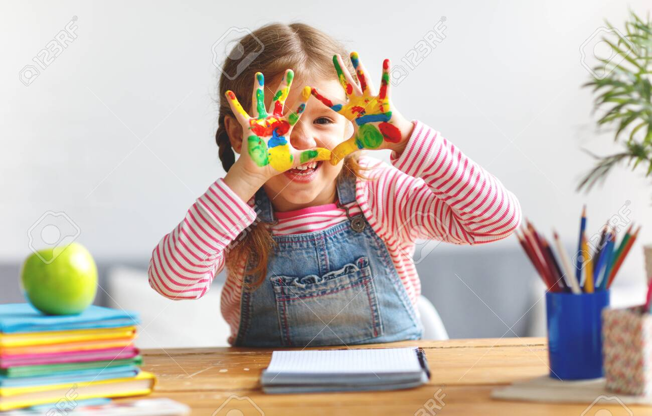 happy funny child girl draws laughing shows hands dirty with paint - 107007273