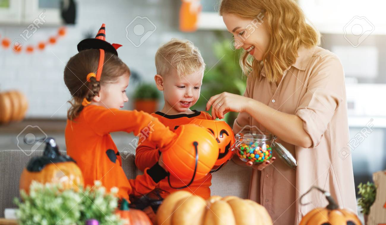 happy Halloween! a mother treats children with candy at home - 109984063