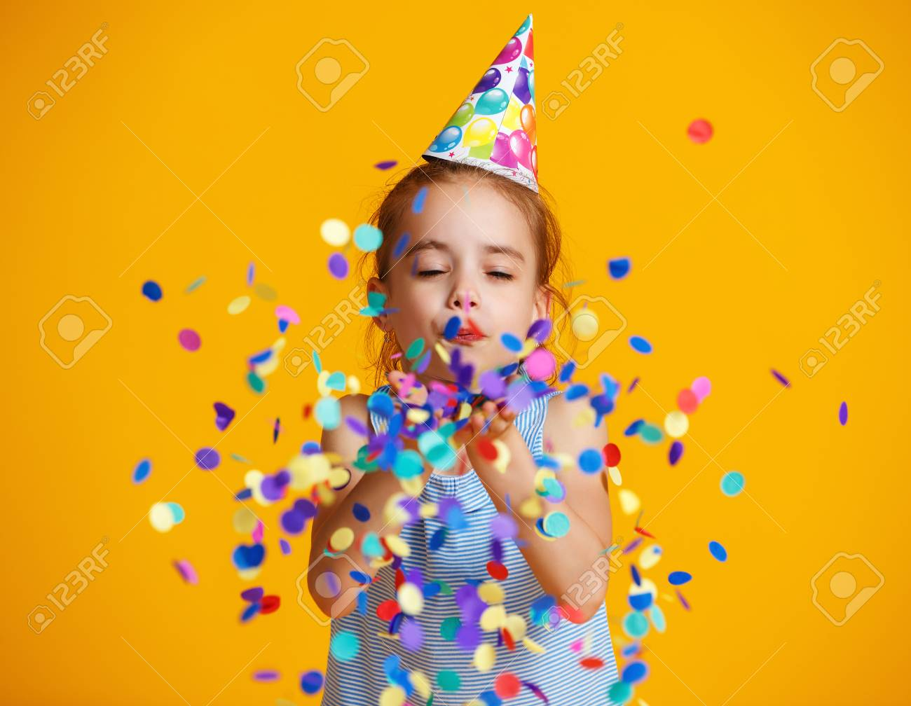 happy birthday child girl with confetti on colored yellow background - 125136174