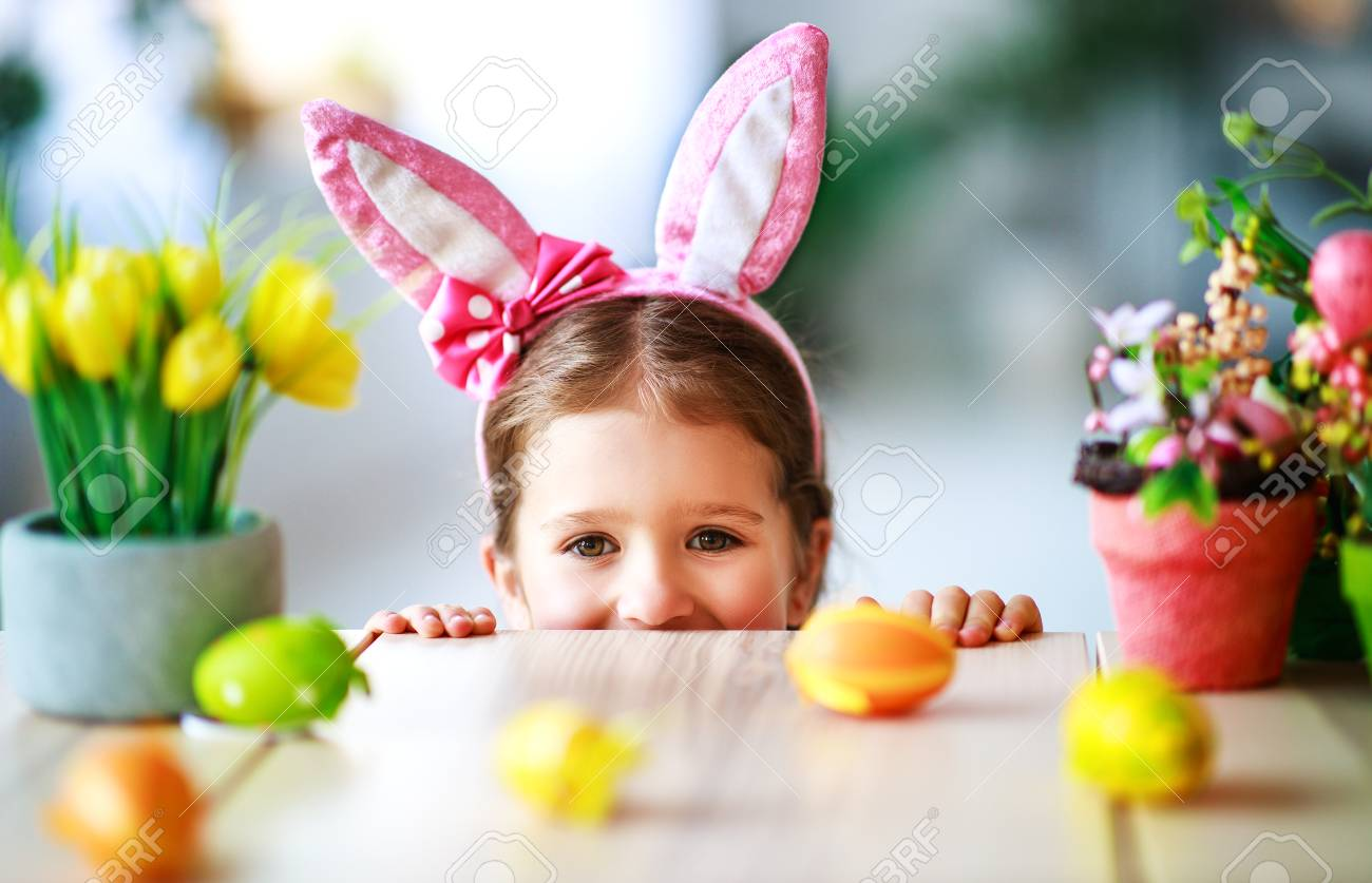 Happy easter! funny child girl with rabbit ears and eggs at home in kitchen - 116644152
