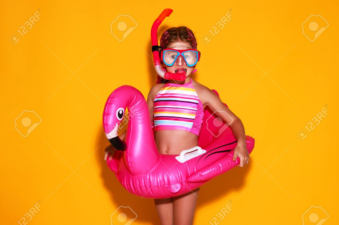 happy child girl in swimsuit with swimming ring flamingo on a colored yellow background - 116646275