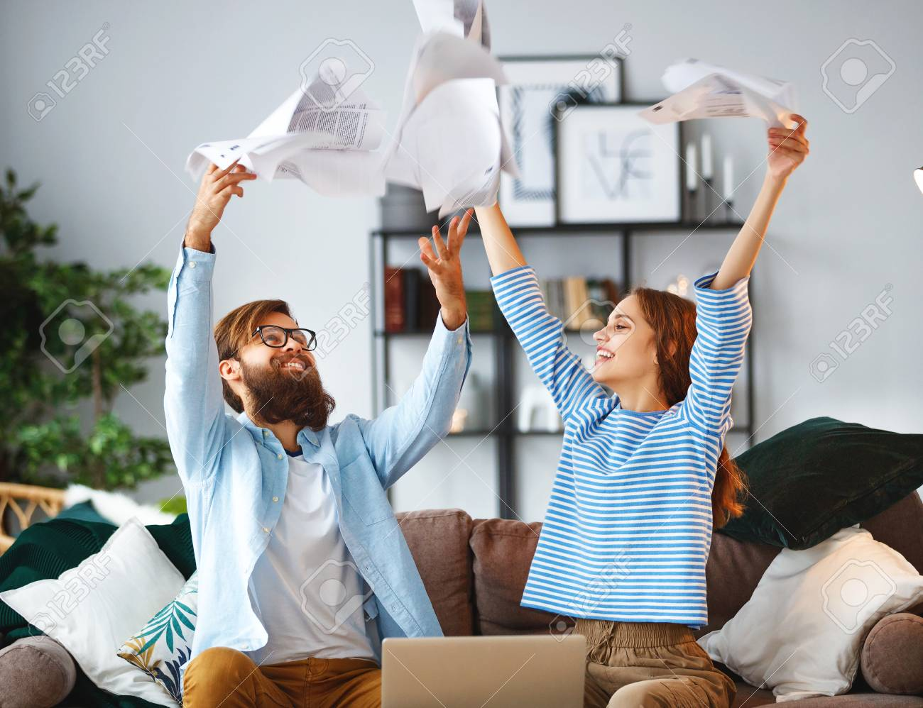 married couple with bills receipts documents and a laptop at home - 118209515
