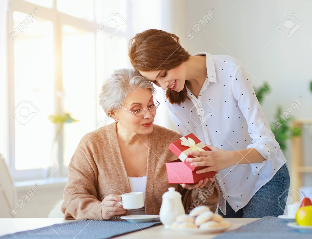 Happy mother's day! An adult daughter gives gift and congratulates an elderly mother on the holiday - 120401839