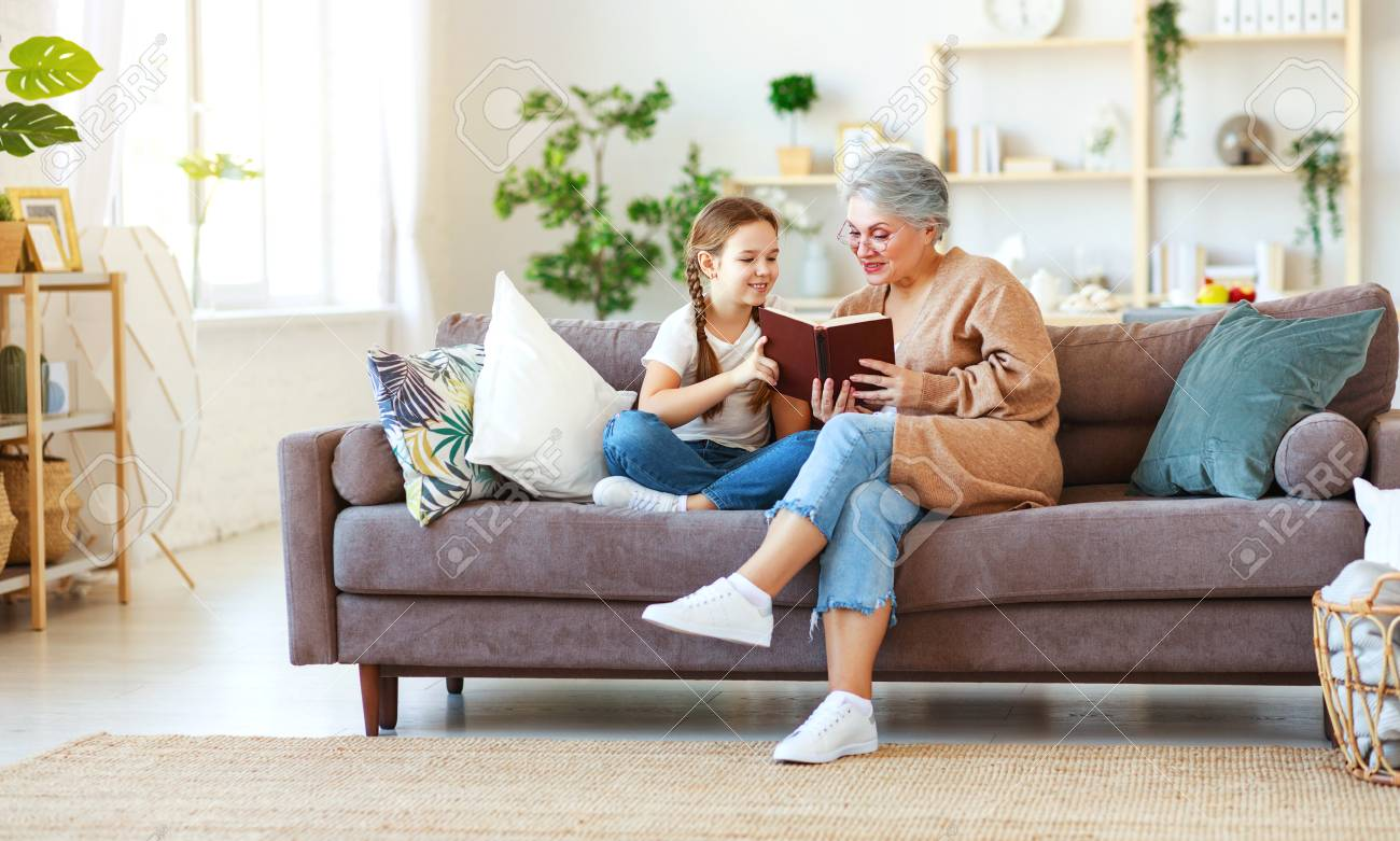 Happy family grandmother reading to granddaughter child book at home - 120628962