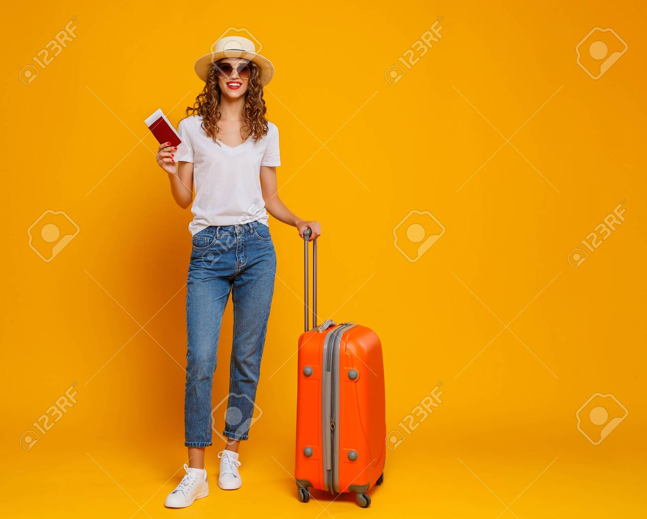 concept of travel. happy woman girl with suitcase and passport on yellow colored background - 124463473