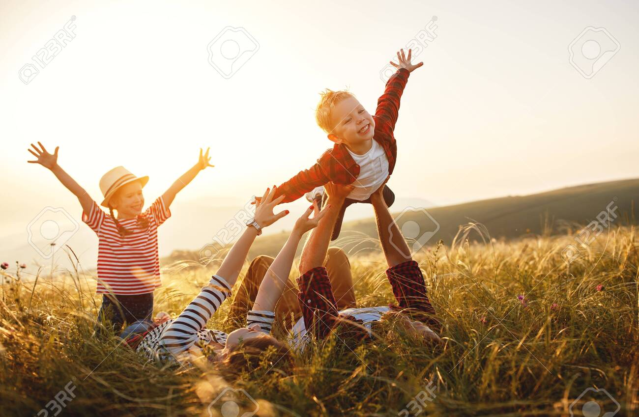 Happy family: mother, father, children son and daughter on nature on sunset - 129115408