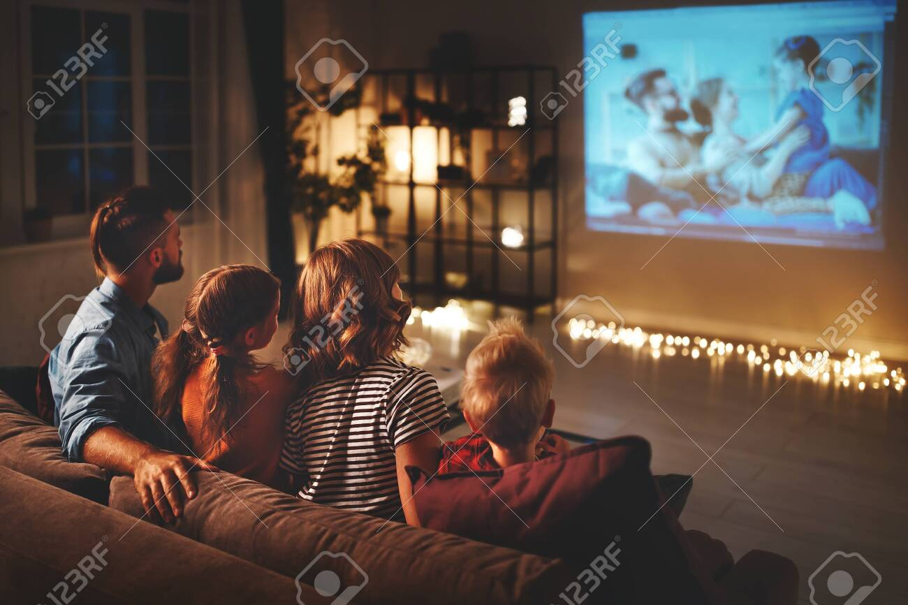 family mother father and children watching projector, TV, movies with popcorn in the evening at home - 130187064