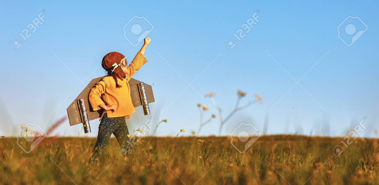 Child pilot aviator with wings of airplane dreams of traveling in summer in nature at sunset - 131211547