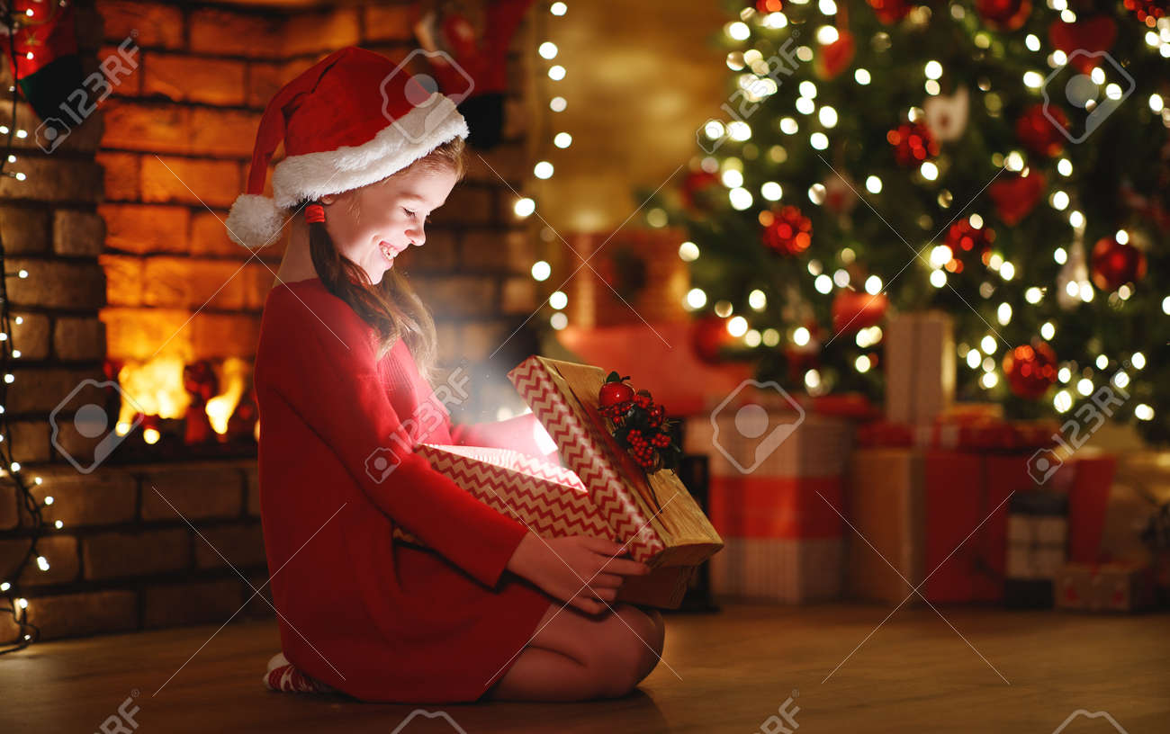 happy laughing child girl with magic gift sitting in front of Christmas tree on Christmas Eve - 134274126