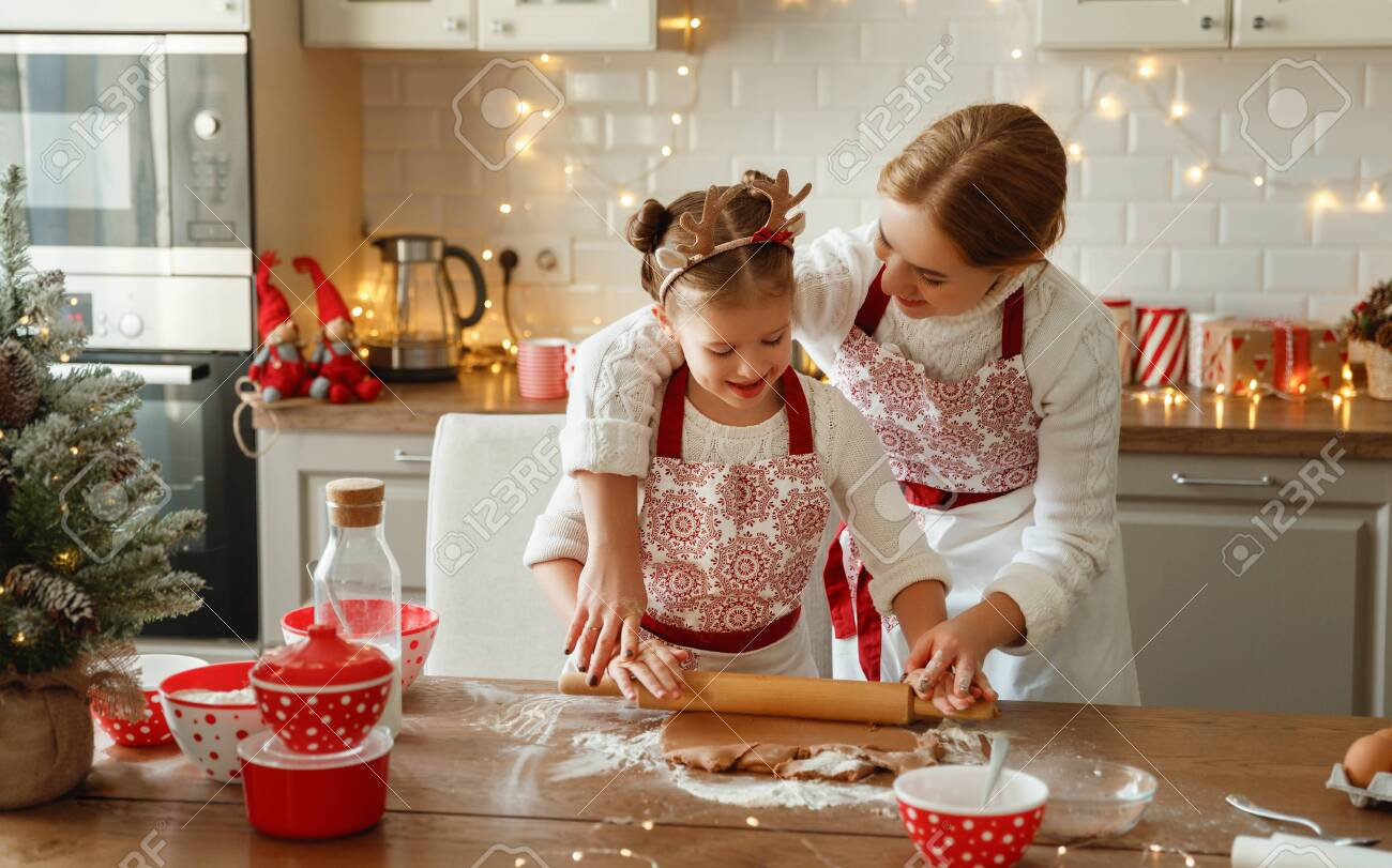 happy funny mother and child daughter bake christmas cookies - 135165172