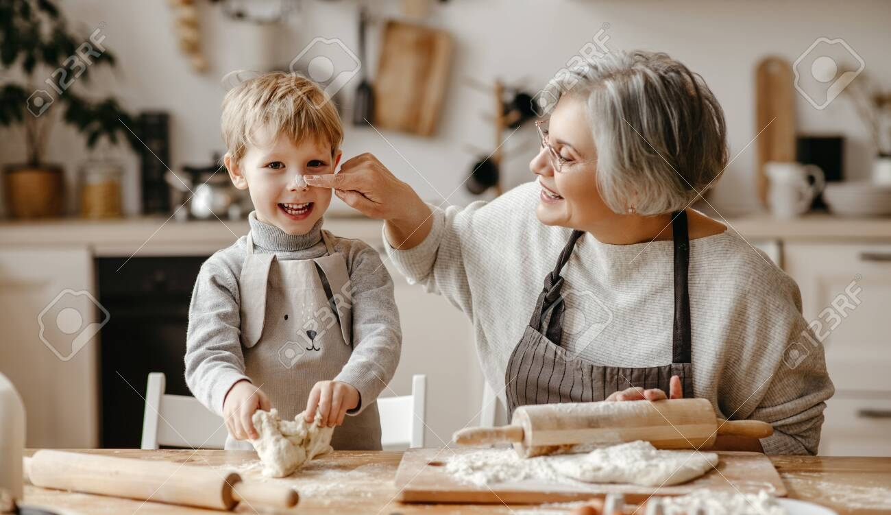 Senior woman and little boy while rolling soft dough during pastry preparation in cozy kitchen at home - 143364210