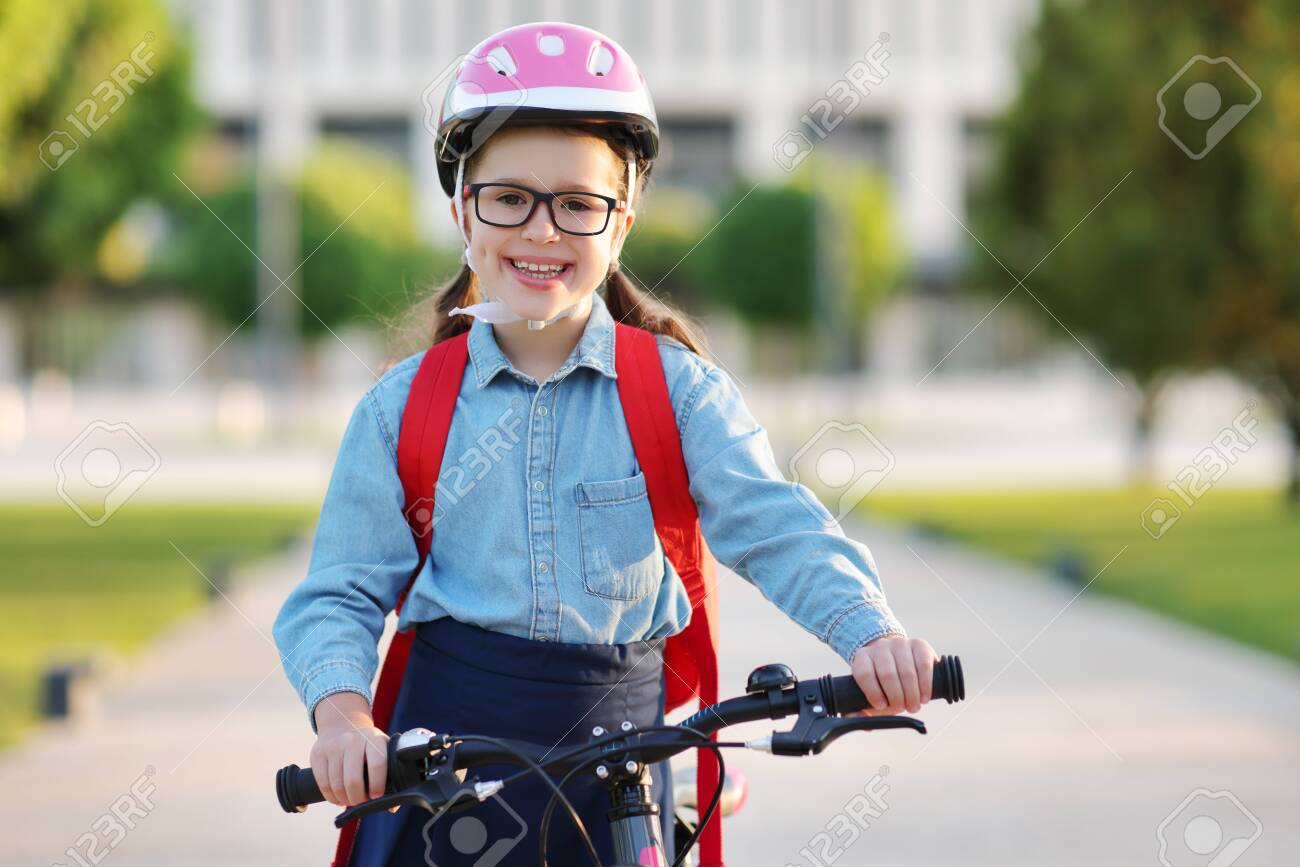 Cheerful child schoolgirl rides to school on a Bicycle in outdoor - 154155997