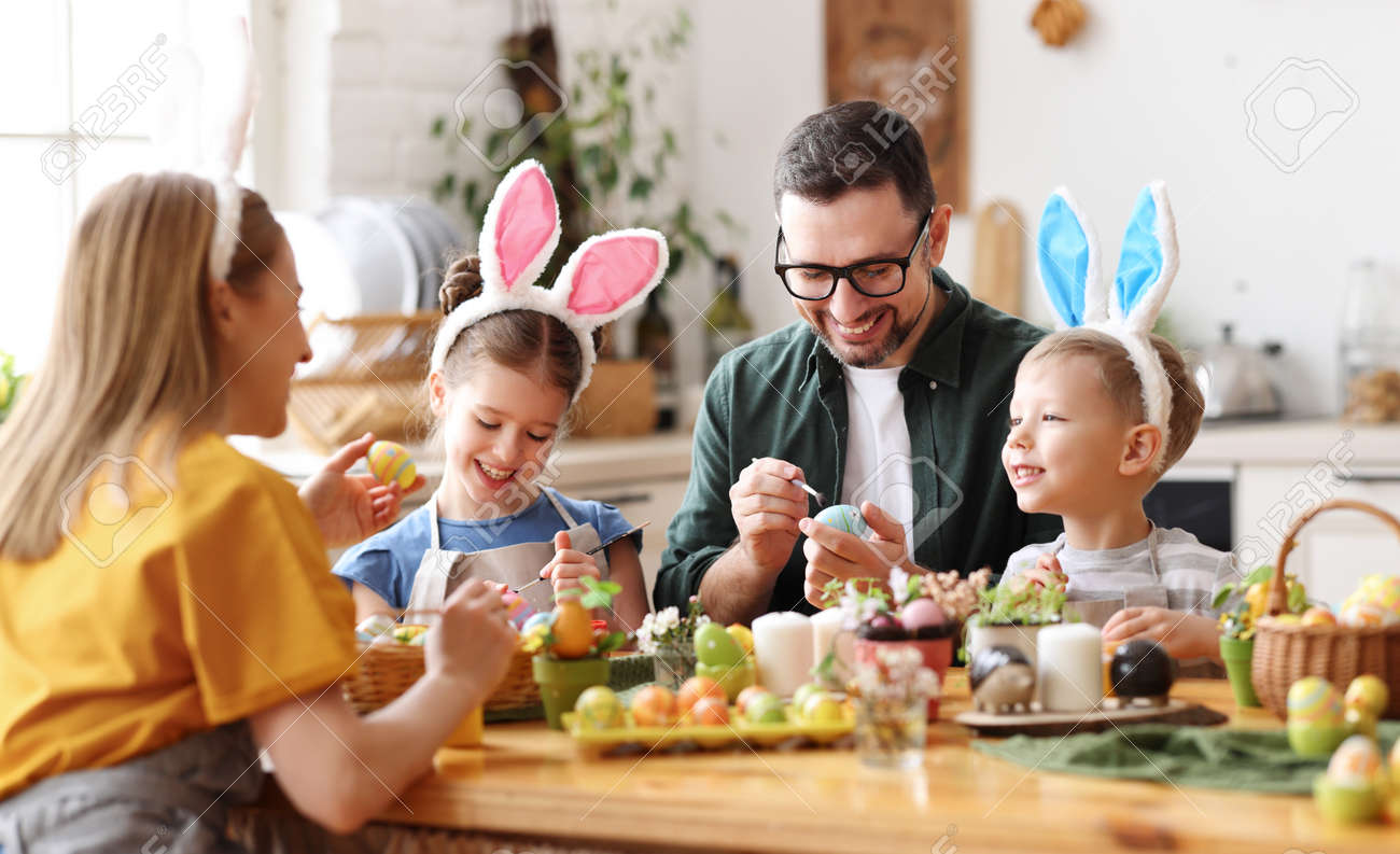Joyful family wearing bunny ears headbands gathering at table in modern light kitchen and paining Easter eggs together - 165248438