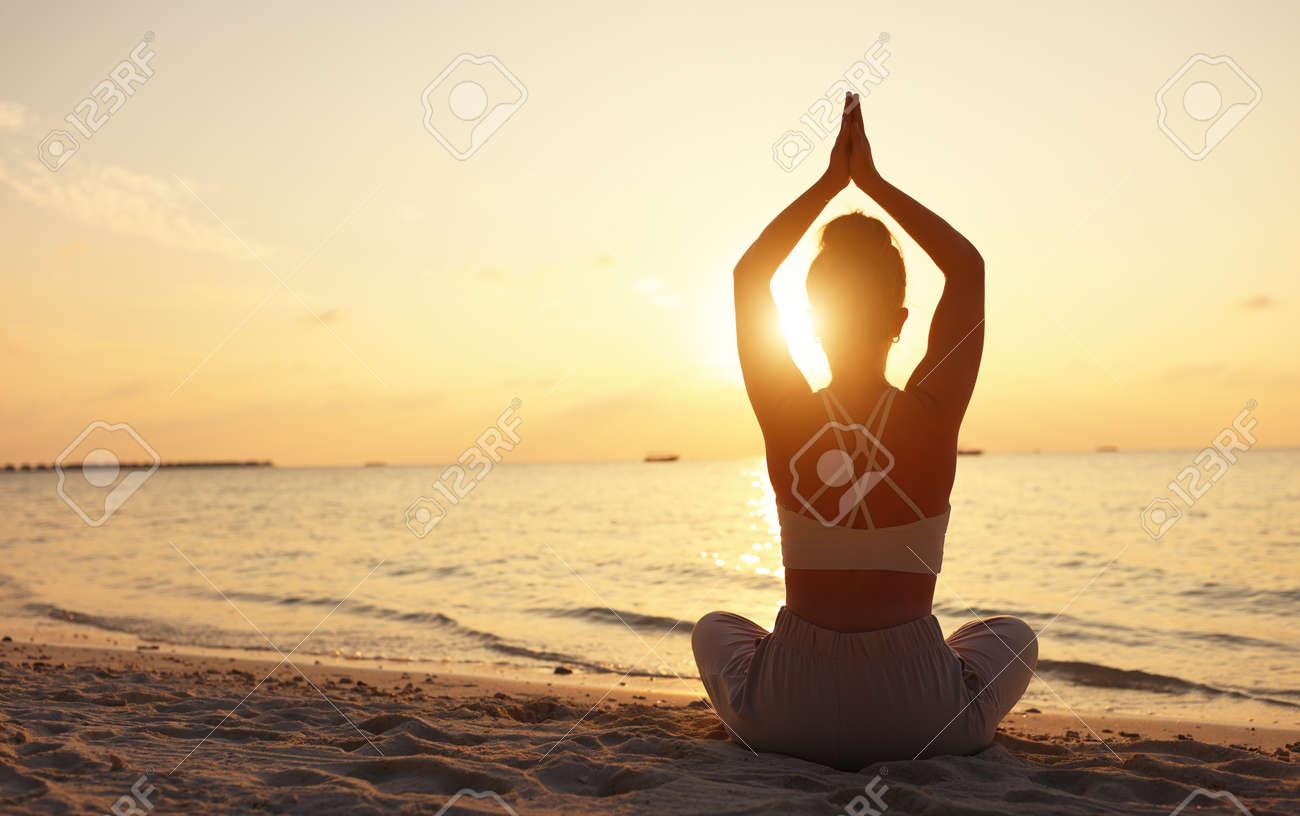 Back view of female sitting in Padmasana while meditating alone on seashore against sky in sundown light - 167579553