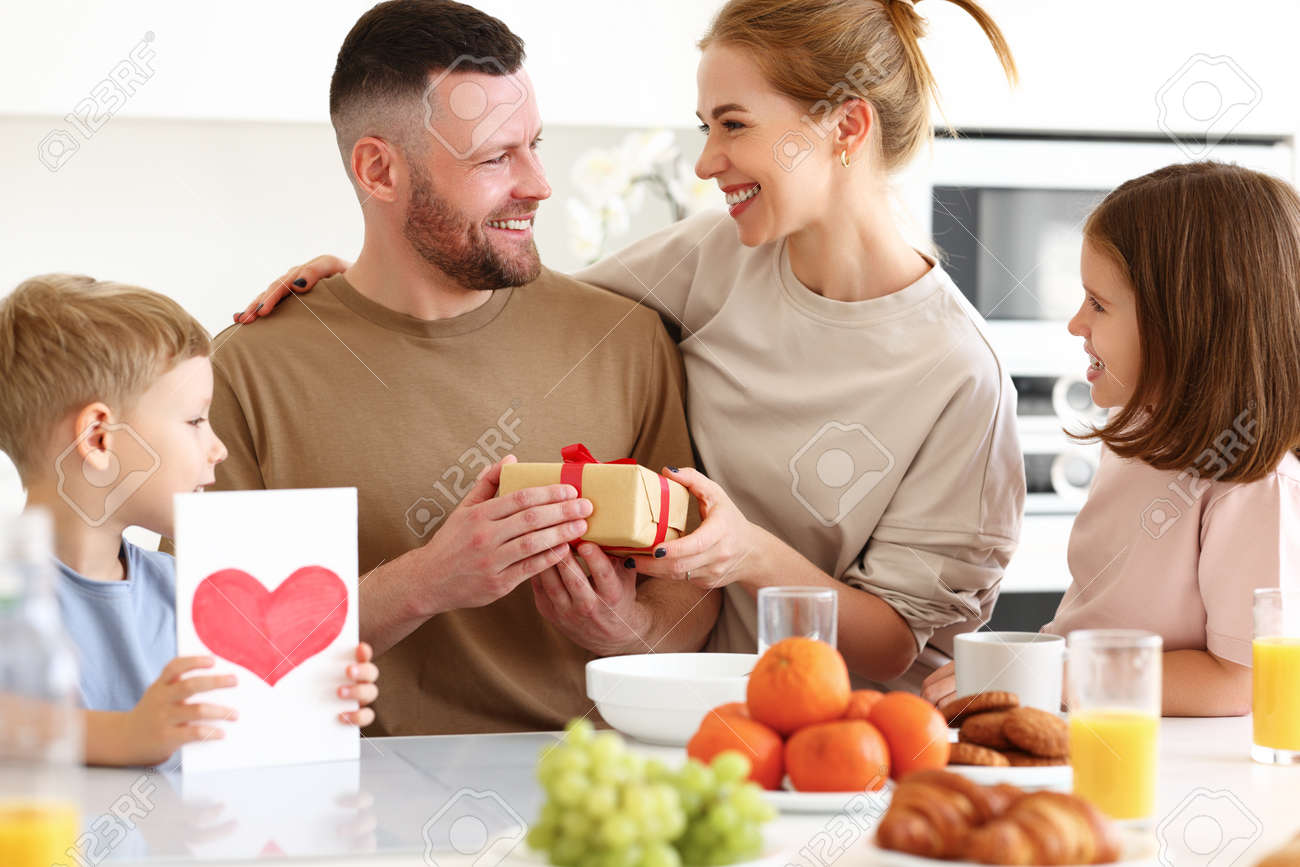 Surpise for daddy. Cute smiling children siblings giving father wrapped gift box and postcard. Young mom congratulating husband with kids while having breakfast in kitchen at home. Family holiday concept - 168303303
