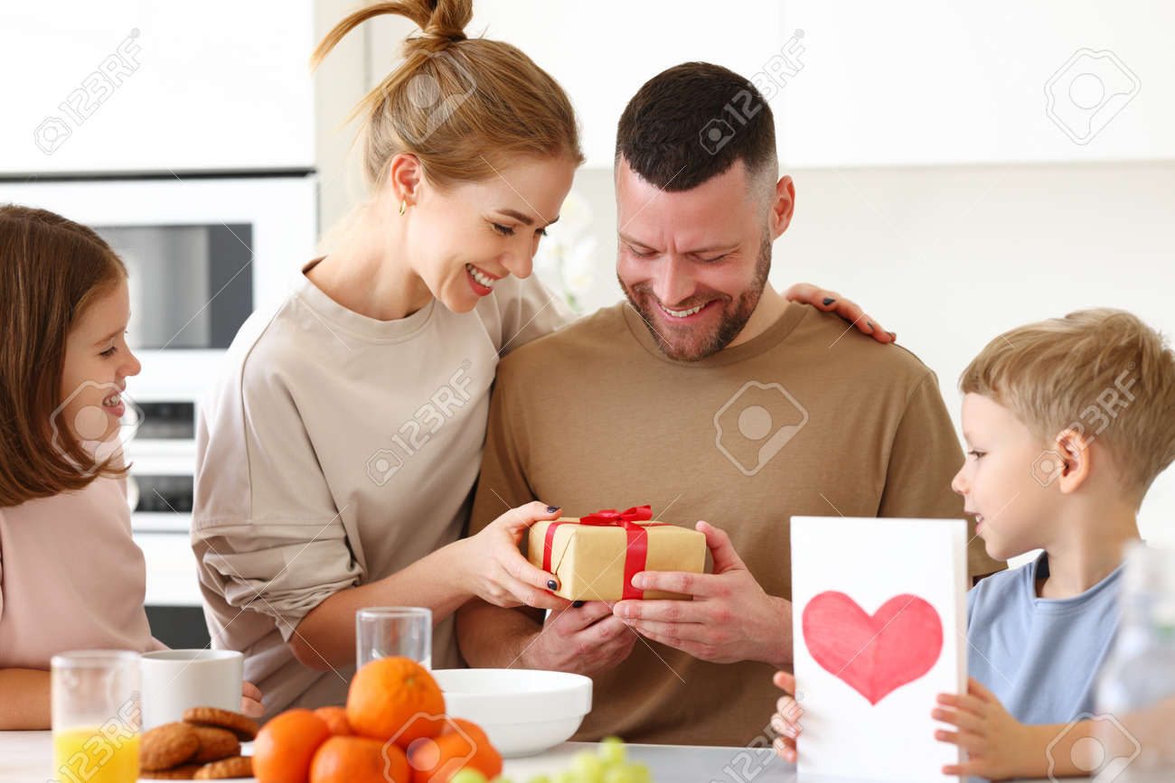 Surpise for daddy. Cute smiling children siblings giving father wrapped gift box and postcard. Young mom congratulating husband with kids while having breakfast in kitchen at home. Family holiday concept - 168303610