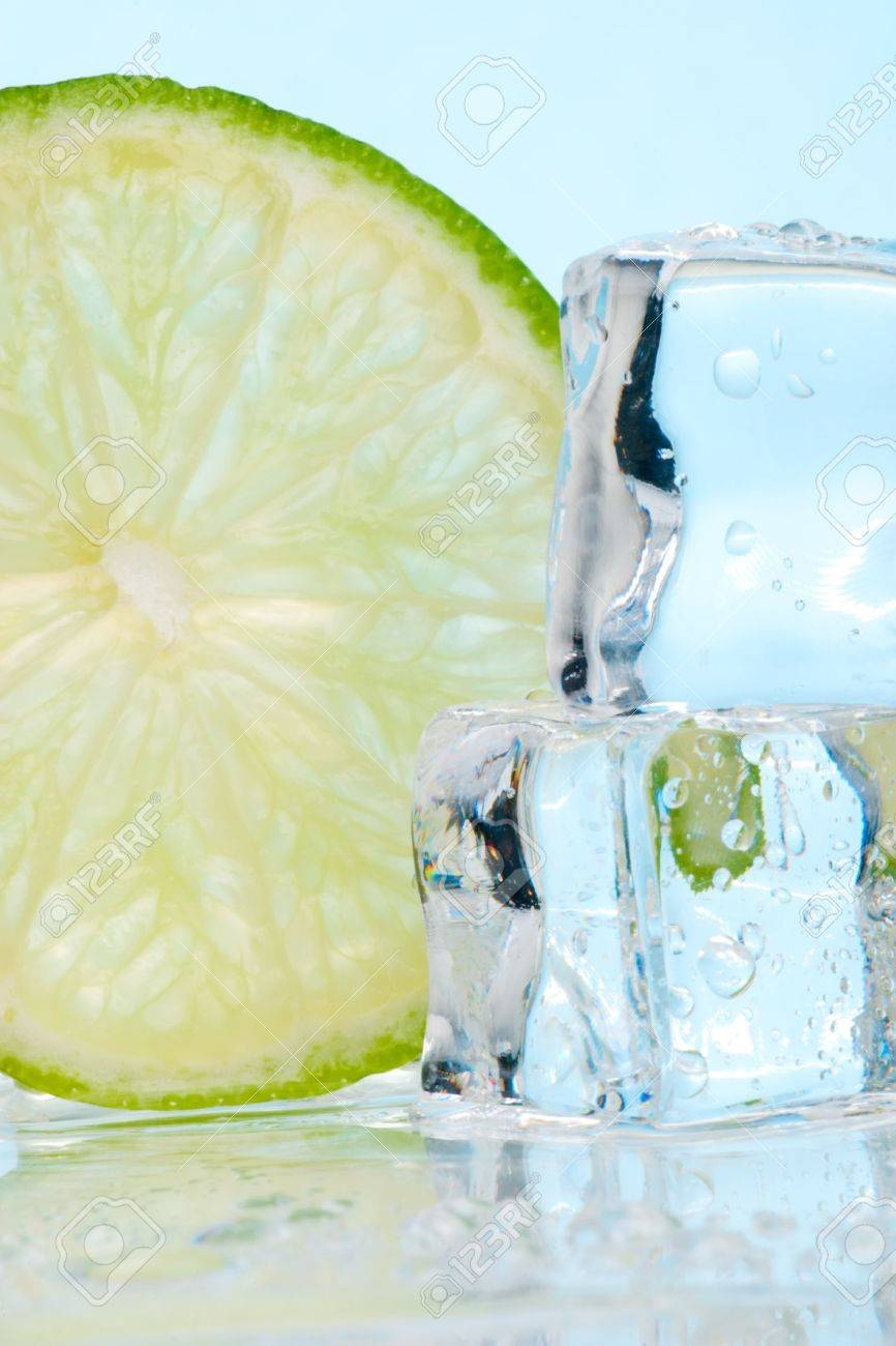 Two stacked ice cubes melted in water and slice of lime on reflection surface ready to be added to a cocktail Stock Photo - 856804