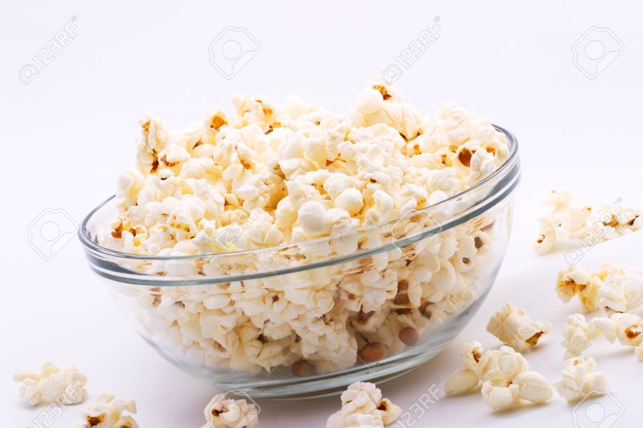 Closeup of glass bowl of popcorn with few peaces throw around Stock Photo - 1172387