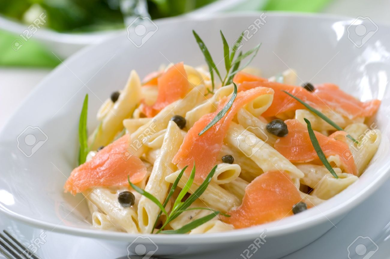 Closeup of plate of Smoked Salmon Penne (tube-shaped pasta) with cappers, tarragon and cheese creamy sauce. Caesar salad and glass of white out of focus. Shallow DOF Stock Photo - 5097207