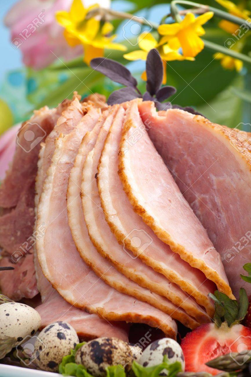 Honey ham on Easter table with quail eggs, tulips and decoration Stock Photo - 6302127