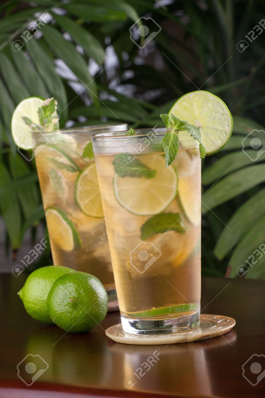 Two glasses of lime and mint iced tea garnished with lime and mint on a table in a restaurant on a tropical beach. Stock Photo - 9531519