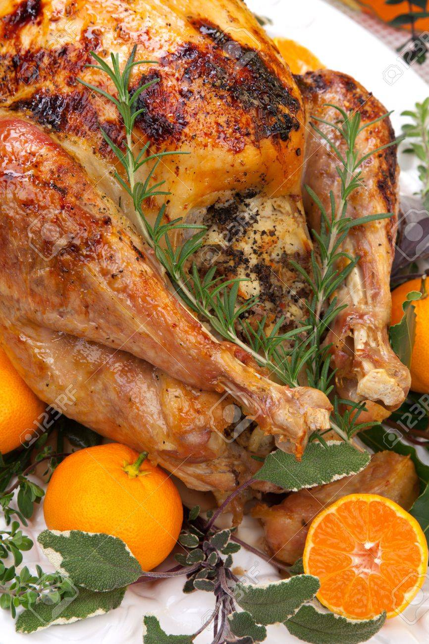 Garnished citrus glazed roasted turkey on holiday table, pumpkins, flowers, and white wine Stock Photo - 15511020