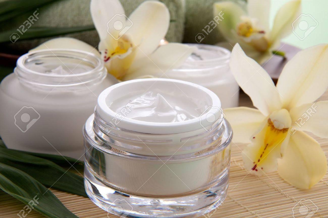 White Cymbidium orchid flower and jar of moisturizing face cream for spa treatment - 15565594