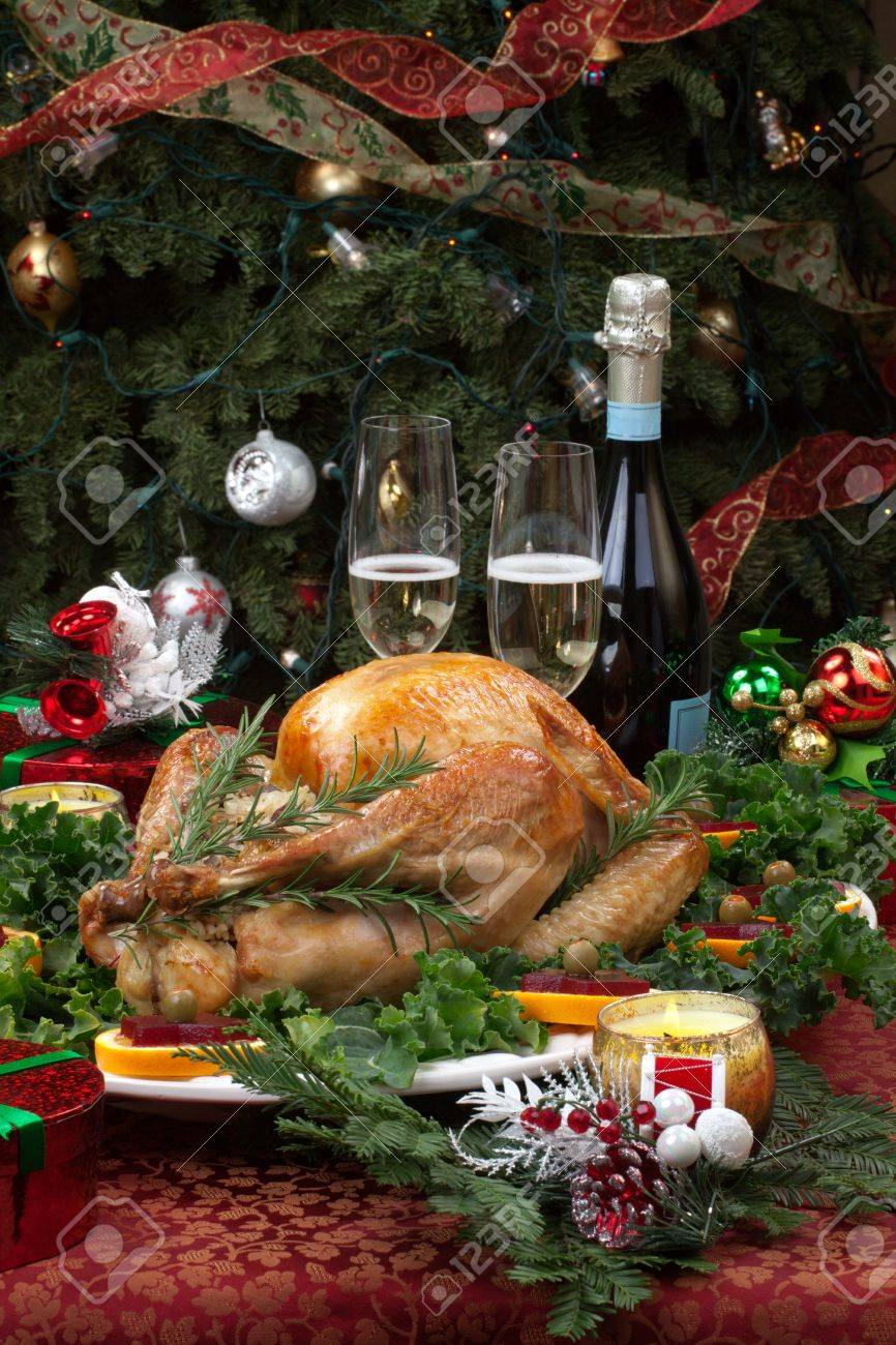 Christmas-decorated table with feast, gifts, roasted turkey, candles, champagne, and Christmas tree on back - 15794120