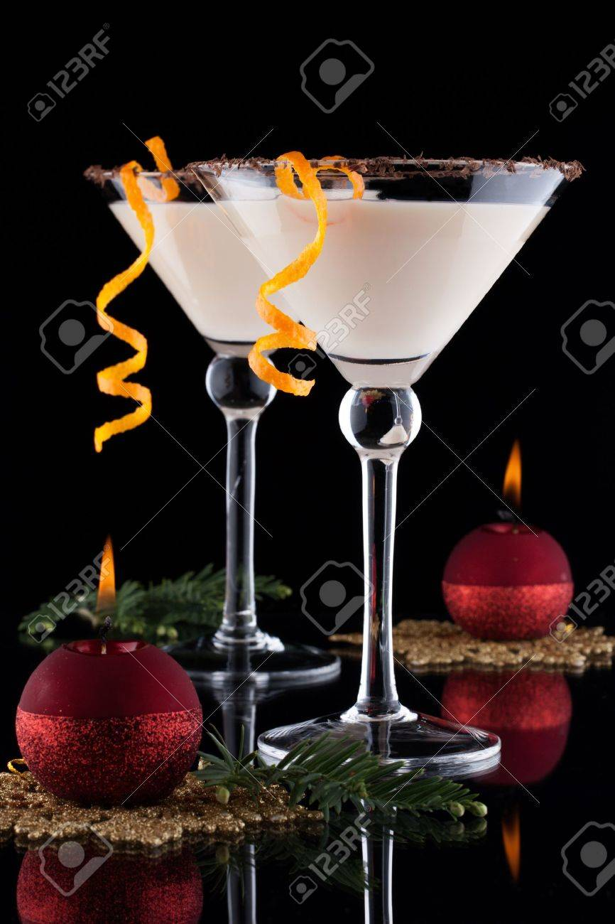 Closeup of Orange Chocolate Dream - festive Christmas cocktail with candles and ornamets over black background Orange twist and chocolate rim Holiday cocktails series - 16542430