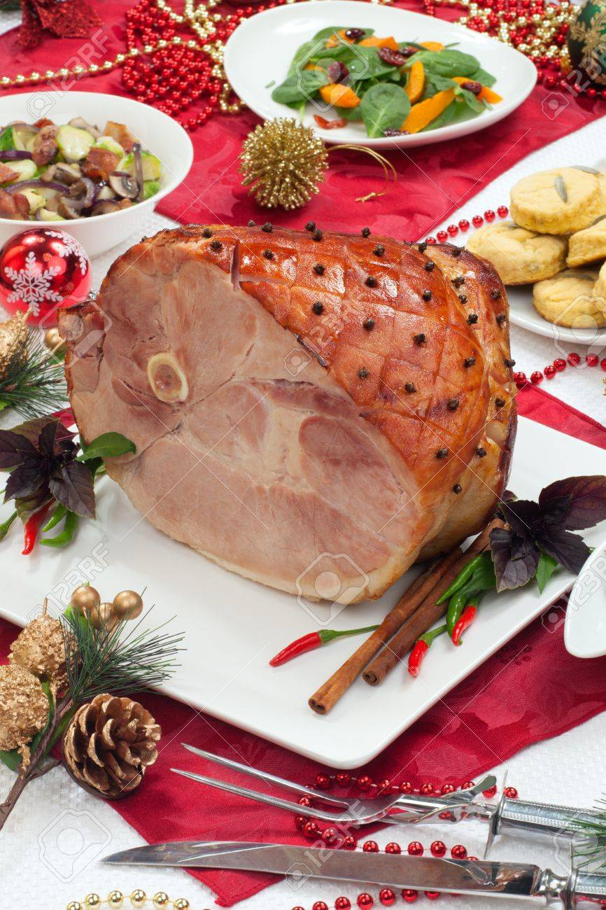 Roasted spiced ham on holiday dinning table, garnished with cloves, cinnamon sticks, hot chili pepper, and purple basil Side dishes and Christmas ornaments around - 16663873