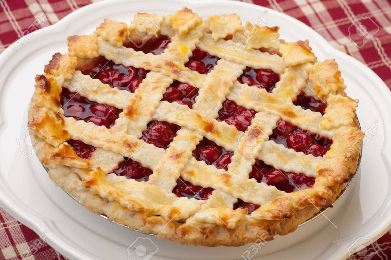 Cherry pie with lattice top on fall themed napkin, and mini pumpkins - 17618176