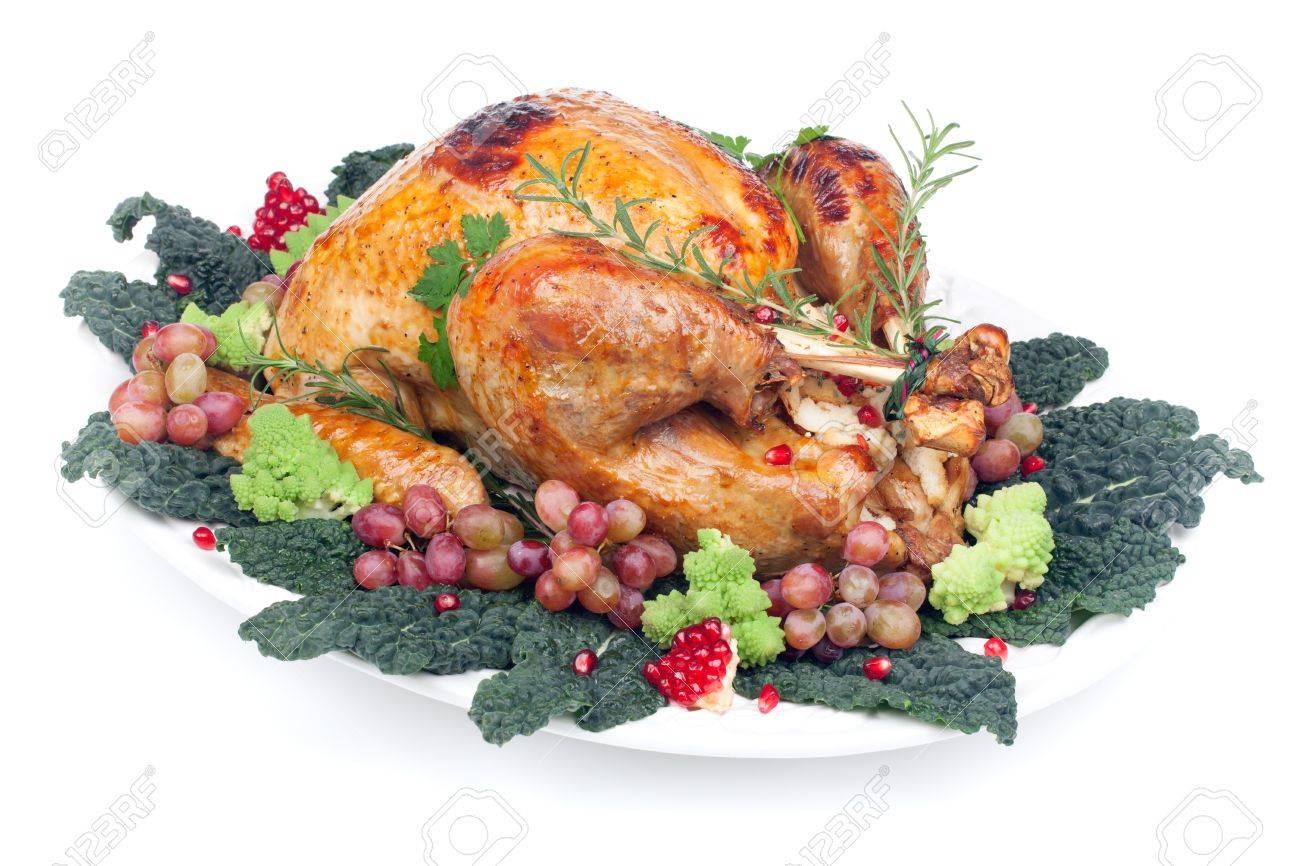 Glazed roasted turkey garnished with grapes, pomegranates, and broccoli over white background Stock Photo - 18138788