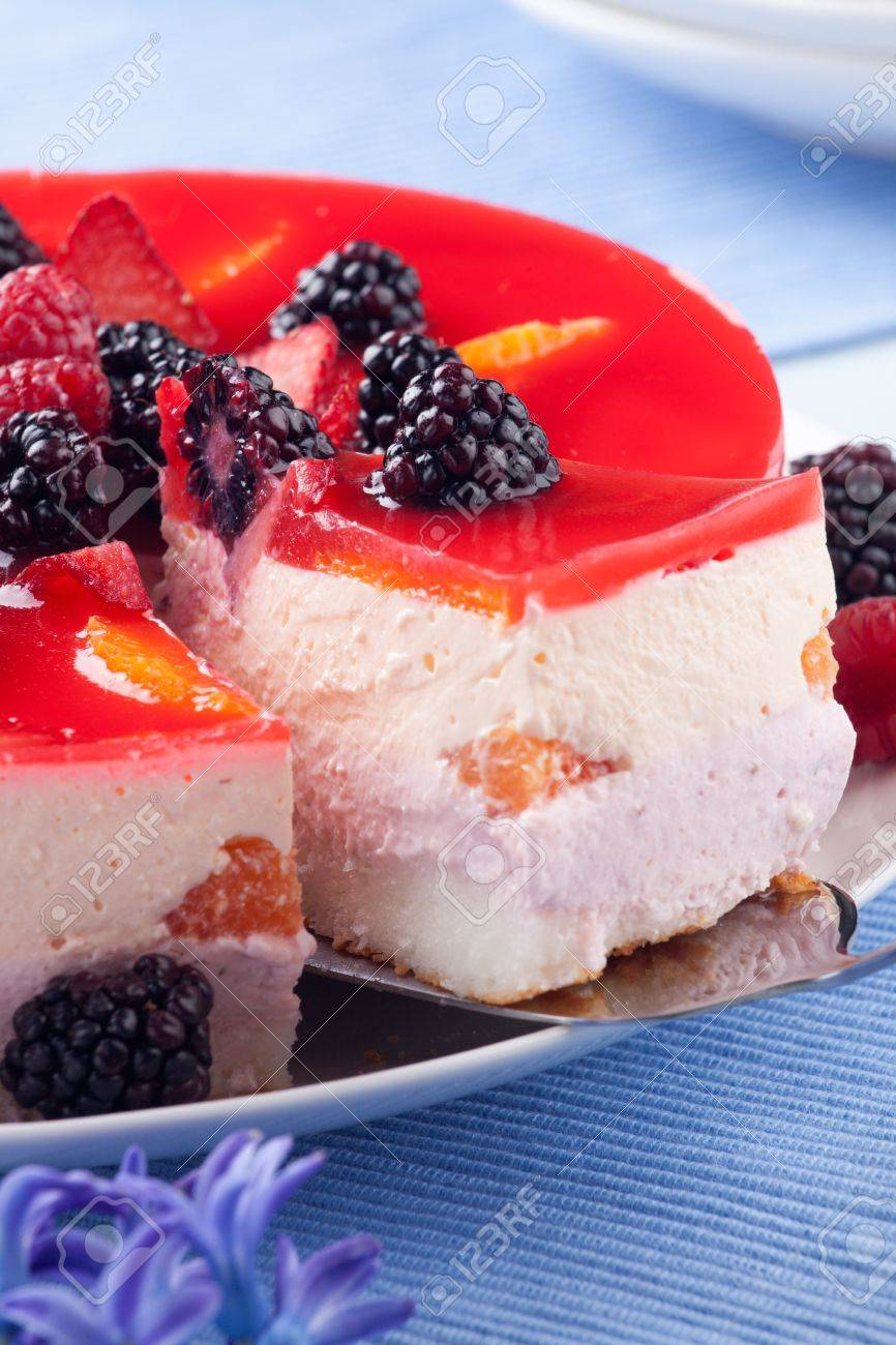Piece of fruit yogurt cake. Cream and yogurt based fruit filling topped with jelly. Raspberries, blackberries, stawberries, and oranges. - 18839868