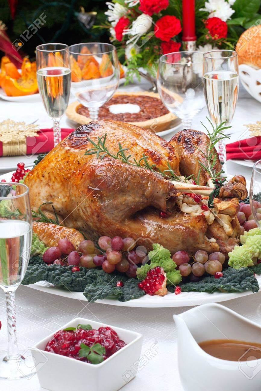 Holiday-decorated table, Christmas tree, champagne, and roasted turkey - 20705194