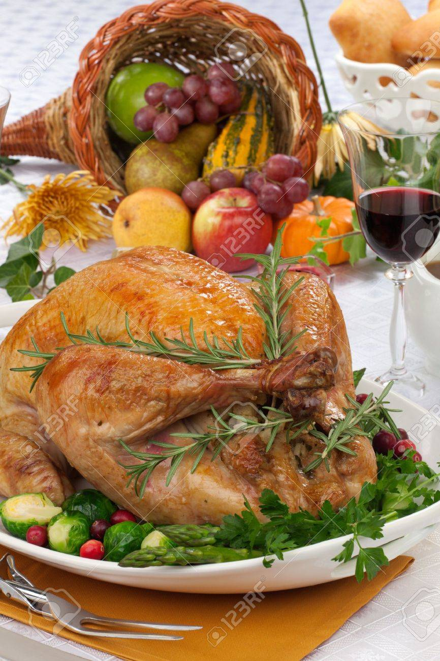 Garnished roasted turkey on fall festival decorated table with horn of plenty and red wine - 21565913