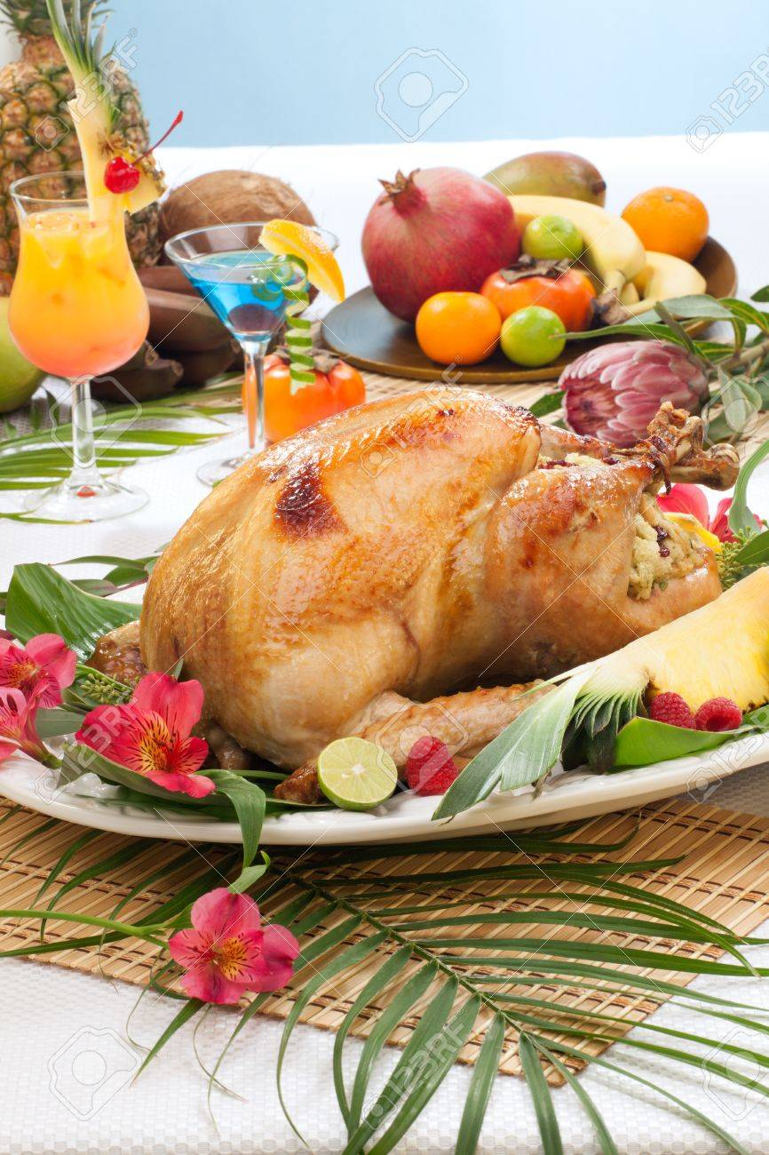 Garnished roasted turkey with tropical fruits, flowers, and refreshing cocktails for Thanksgiving - 21565947