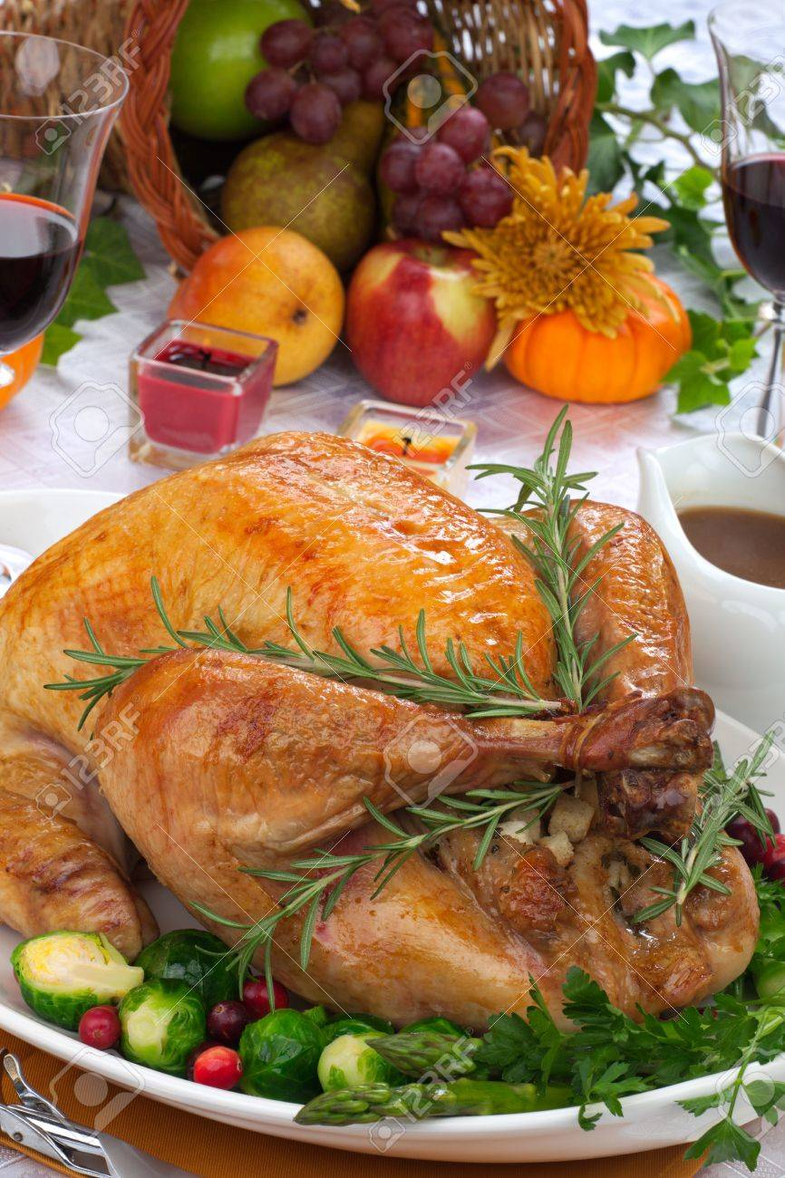 Garnished roasted turkey on fall festival decorated table with horn of plenty and red wine - 22026045