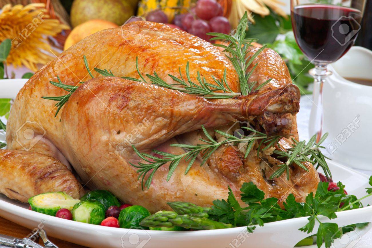 Garnished roasted turkey on fall festival decorated table with horn of plenty and red wine - 22026046