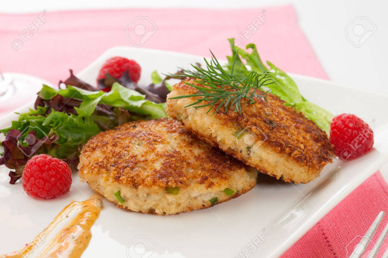 Two crab cakes appetizer garnished with spicy sauce, green salad, and raspbery - 22106347